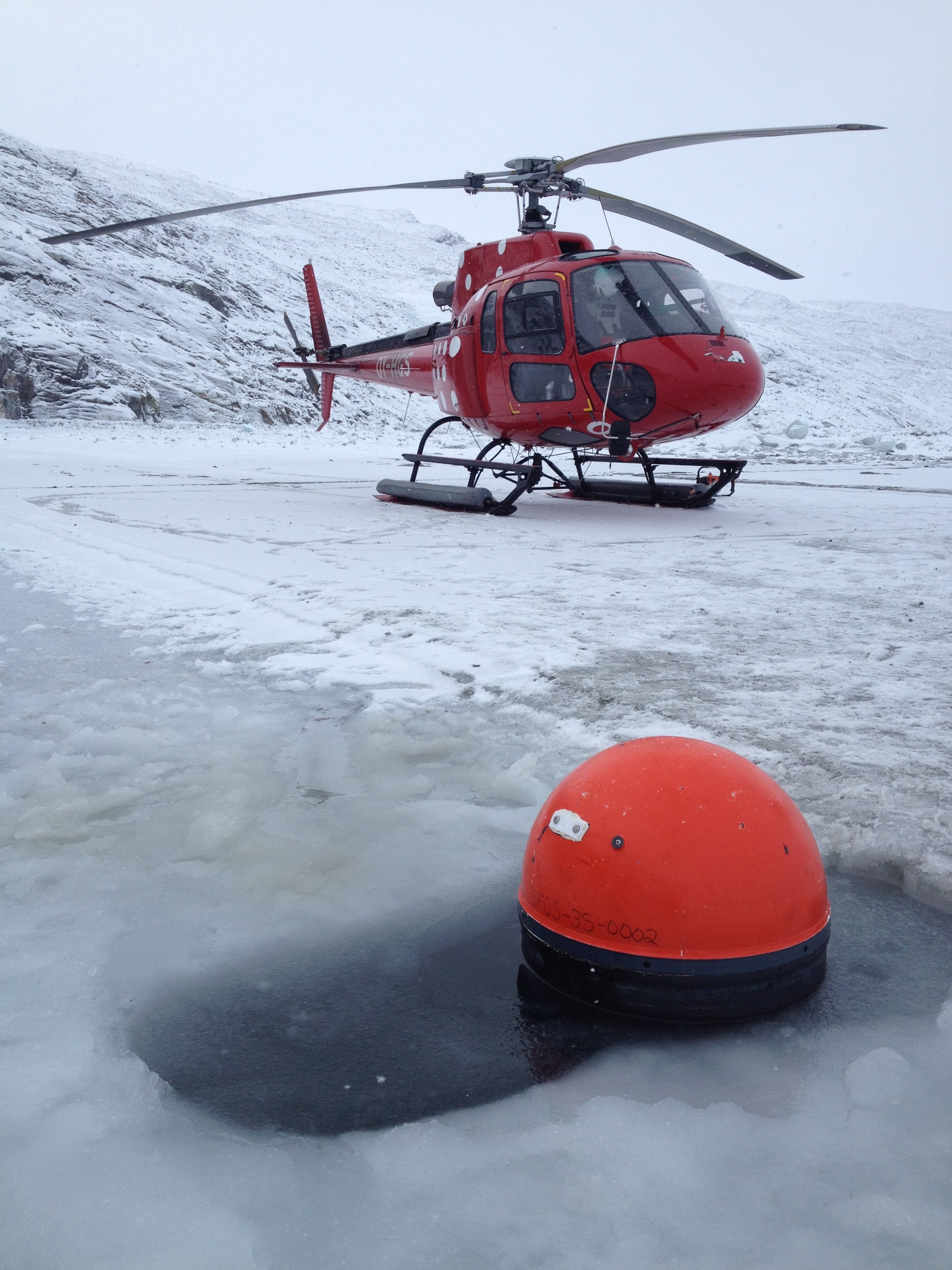 Drifter deployment through the ice in February 2014 (Photo courtesy of Kunuk Lenert).